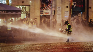 A demonstrator wearing a yellow vest is blasted with a police water canon on the Champs-Elysees in Paris on Saturday.