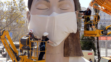 Workers place a mask on the figure of the Fallas festival in Valencia – the festival is cancelled.