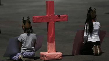 "Girls sit next to a cross to remember murdered women in Mexico City, during the national ""A day without women"" strike on Monday."