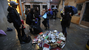 "Young volunteers help the clean up, throwing out damaged books from renowned bookstore ""Acqua Alta"" in Venice."