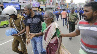 Sri Lankan elderly woman is helped near St Anthony's Shrine after a blast in Colombo, Sri Lanka.