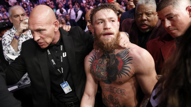 Conor McGregor is led away by security after the post-fight drama.