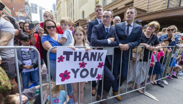 """Erin Marsh, 9, is seen holding a """"Thank You"""" sign in the crowd during the Anzac Day parade in Brisbane."""