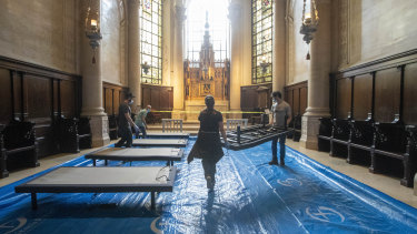 Volunteers place beds in a chapel while building a field hospital at the Cathedral of St. John the Divine, in New York.