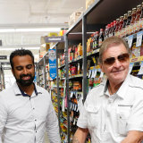 Altona IGA owner Hitesh Palta, left, with a customer. His supermarket was the first to introduce an elderly-only shopping hour.