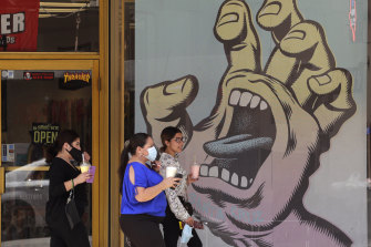 People wearing masks to protect against the spread of COVID-19 pass a mural on a business that has reopened in San Antonio, Texas, where cases of COVID-19 have spiked.