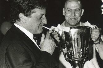John Elliott lights up as ex-Carlton player Des English holds the premiership cup.