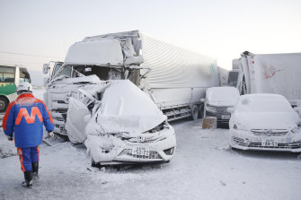 Damaged vehicles are covered in snow following the huge pile-up.