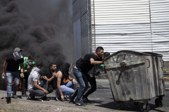 Palestinian demonstrators take cover during clashes with Israeli forces at the Hawara checkpoint, south of the West Bank city of Nablus, on Friday.