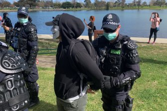 Police arrest a protester at anti-lockdown at Albert Park Lake.