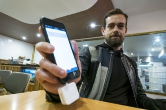 Square co-founder Jack Dorsey, who also co-founded Twitter, demonstrates the company's credit card reader.