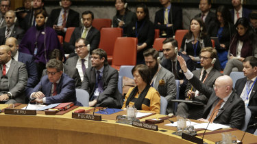 Russian Ambassador to the United Nations Vasily Nebenzya, right, votes against a resolution concerning Venezuela during a Security Council meeting at UN headquarters in New York.