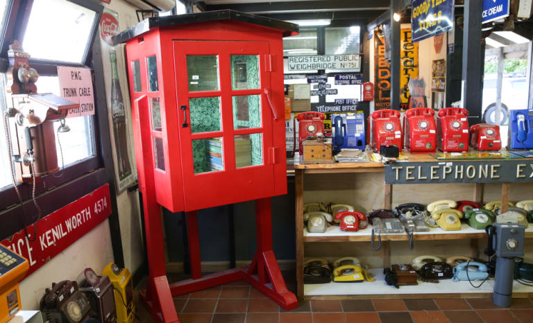 """A rare half telephone box - known as the """"bum freezer"""" because it offered shelter only to the user's upper body - and other vintage phones for sale."""