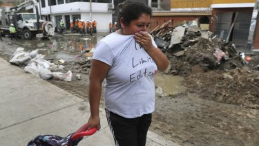 A woman covers her nose as she passes a street flooded with sewage water in Lima's San Juan de Lurigancho district.