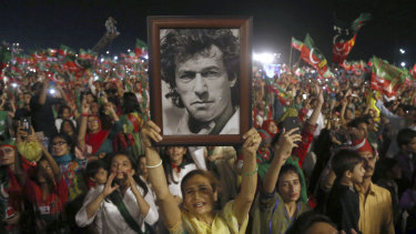 A woman supporter of Tehreek-e-Insaf party raises a picture of her party's leader Imran Khan during an election campaign rally in Karachi.