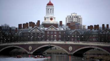 Rowers paddle down the Charles River past the campus of Harvard University in Cambridge, Massachusetts.