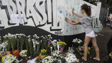A student places her handprints on a wall at Raul Brasil State School.