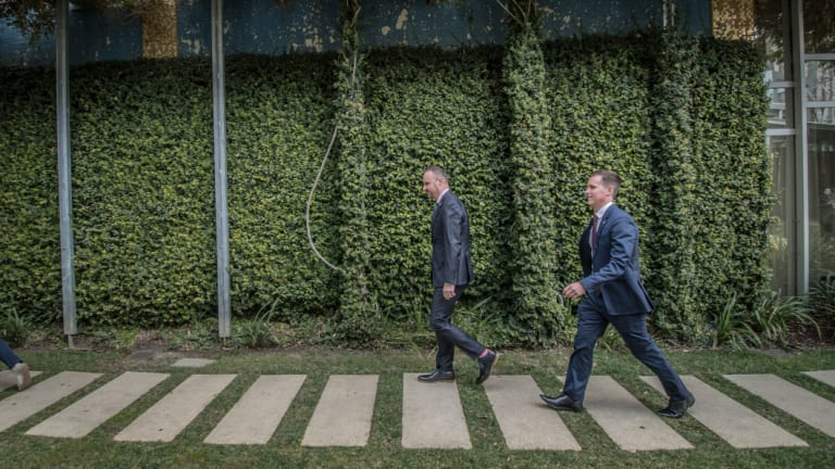 ACT Chief minister Andrew Barr and his new minister Chris Steel exit the courtyard of the ACT Legislative Assembly.