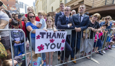 "Erin Marsh, 9, is seen holding a ""Thank You"" sign in the crowd during the Anzac Day parade in Brisbane."