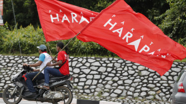 Supporters ride with flags of Pakatan Harapan (Alliance of Hope) as Anwar Ibrahim arrives at a polling station in the southern coastal town of Port Dickson.