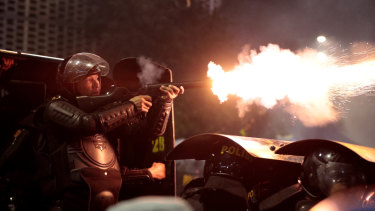 A riot police officer fires his tear gas launcher at supporters of Indonesian presidential candidate Prabowo Subianto during a clash in Jakarta, Indonesia.