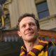 Actor Gareth Reeves in his Harry Potter scarf in front of the Princess Theatre.