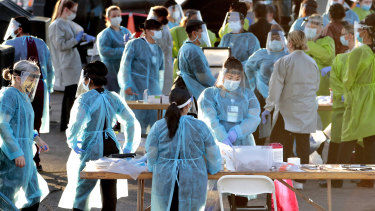 Medical personnel prepare to test hundreds of people lined up in Phoenix in the US on the weekend.