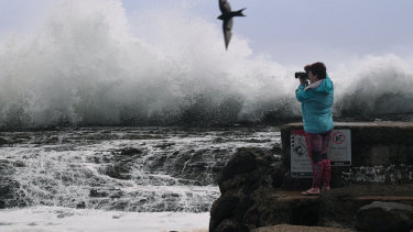 A woman takes photographs of large surf at Snapper Rocks on the Gold Coast, Friday, February 22, 2019.  Huge swells and high tides are pummeling south-east Queensland beaches as Cyclone Oma sits off the Queensland coast.