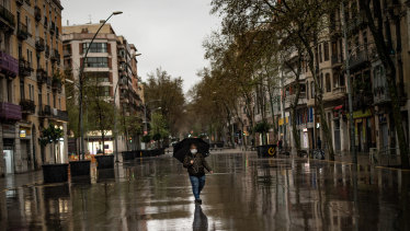 A woman wearing a protective mask walks on an empty street in Barcelona, Spain.