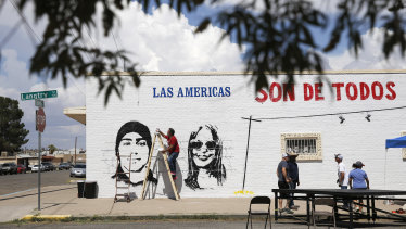 """Manuel Oliver works on a mural in El Paso, Texas. It reads: """"The Americas belong to everyone"""". The shooting that killed more than 20 people on Saturday is being handled as a domestic terrorism case."""