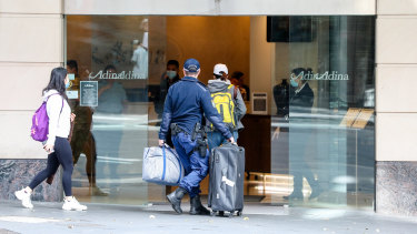 Travellers  returning from overseas escorted to hotel quarantine in Sydney.
