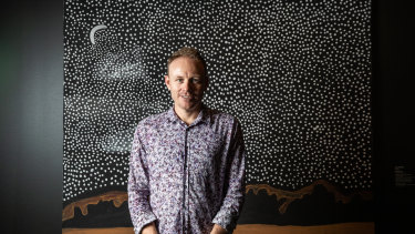Luke Scholes, curator of Aboriginal art and material culture at the Museum and Art Gallery of Northern Territory, in front of Peters' artwork Garnkiny.
