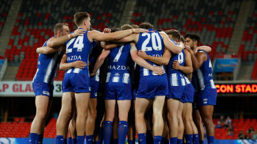 The Kangaroos huddle during the 2020 AFL Round 18 match.