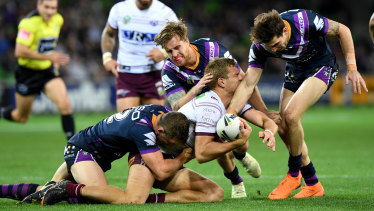 Ryan Hoffman, Cameron Munster and Curtis Scott bring down Manly's Tom Trbojevic on a messy night at AAMI Park.