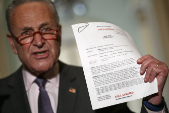 Senate Minority Leader senator Chuck Schumer holds up a copy of a released transcript of a phone call between President Donald Trump and the President of Ukraine.