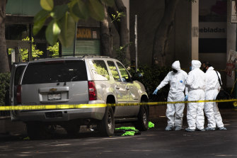Forensic investigators examine a vehicle following the assassination attempt in Mexico City.