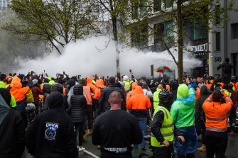 People inside the CFMEU office fend off protesters with fire extinguishers on Monday.