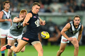 Patrick Cripps of the Blues kicks whilst being tackled by Willem Drew of the Power.