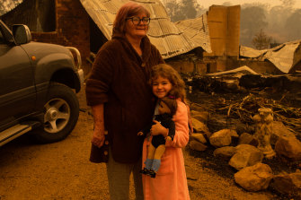 Barbara Rugendyke with one of her children, in front of their property which was devastated by bushfires.
