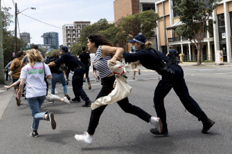 Police clear protesting students from the road at Sydney University.