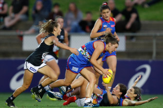 Georgia Gee chases Kirsty Lamb in Friday night's AFLW clash between the Blues and Dogs.