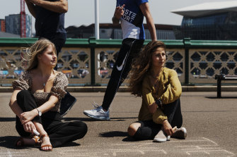 A passer-by makes a rude gesture as Elizabeth Payne, left, and Carla Sieck chalk an anti-harassment message on Pyrmont Bridge.