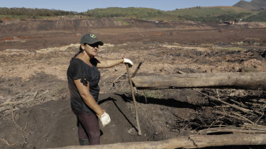 Tereza Nascimento pauses as she digs in search of her missing brother Paulo Santos' body, using garden tools, at the site of the Brumadinho dam disaster.