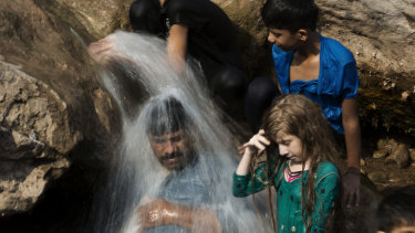 A family cools off in a stream during a heat wave in Pakistan in 2017.