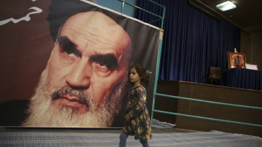A girl walks past a poster of Ayatollah Ruhollah Khomeini, at a mosque where he made speeches, in northern Tehran, Iran. The memory of Khomeini, who died in 1989 at the age of 86, looms large over Tehran.