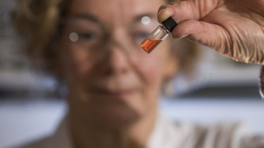 Australian National University biogeochemistry lab manager Janet Hopeholds a vial of pink coloured porphyrins representing the oldest intact pigments in the world.