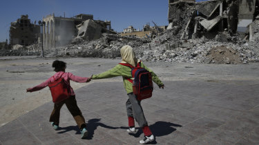 Syrian students run in front of buildings that were destroyed last summer during fighting between US-backed Syrian Democratic Forces fighters and Islamic State militants, in Raqqa, Syria.