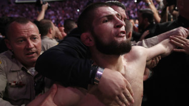 Khabib is held back outside the cage after the fight.