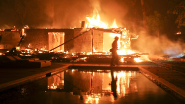A firefighter walks by a burning home in Malibu, California.