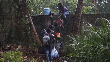 Haitian migrants jump the wall of the Mesoamericana fairgrounds to look for food, in Tapachula, Chiapas state, Mexico.